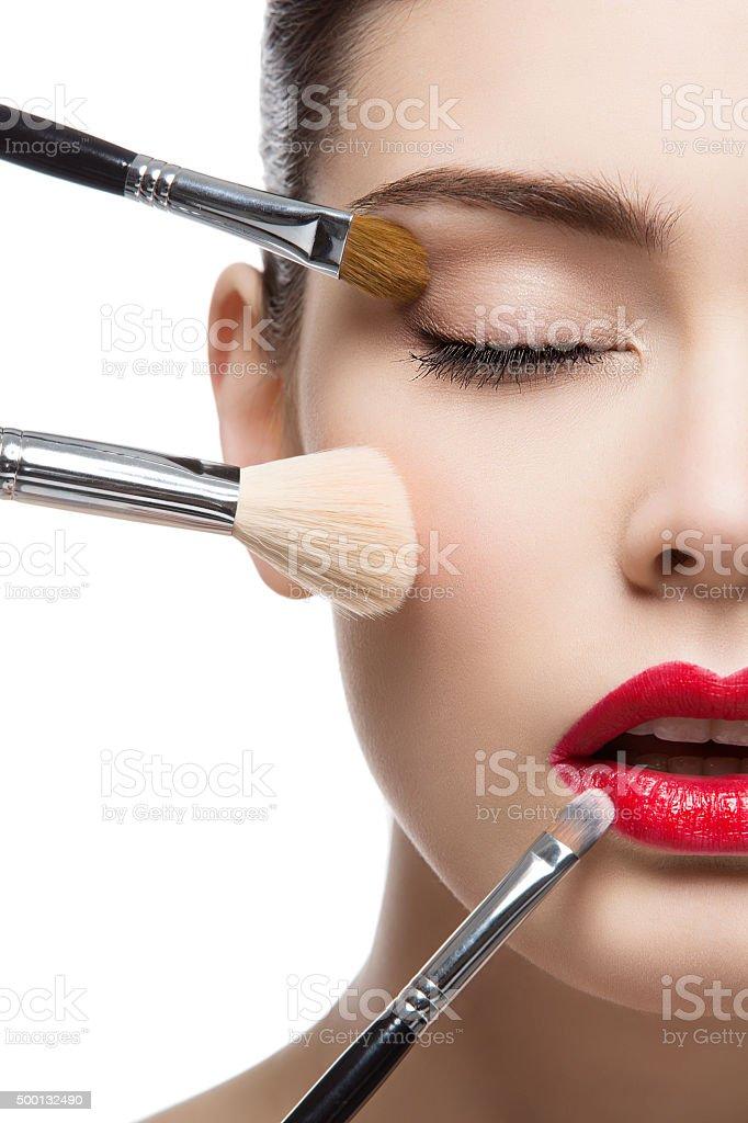 Beautiful girl with makeup brushes stock photo