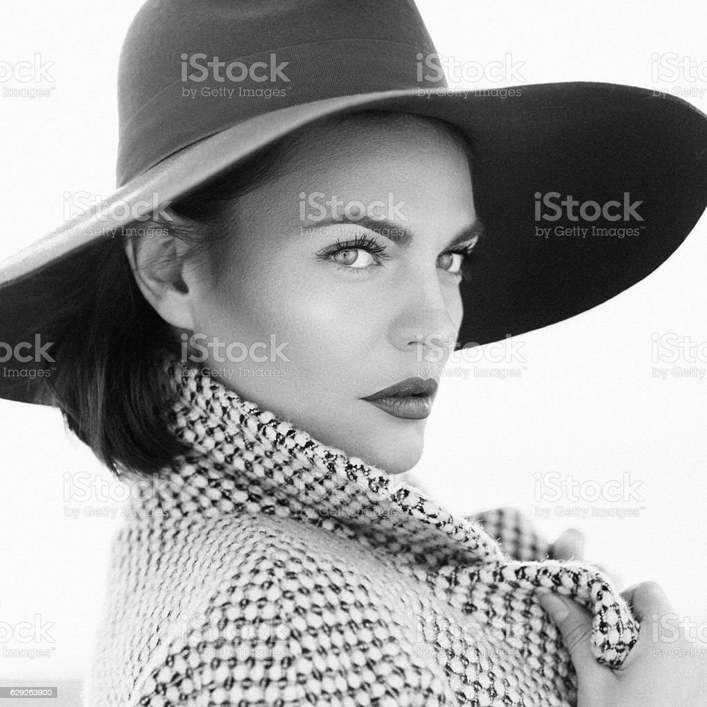 Beautiful girl with make-up, dressed in old-fashioned coat and hat stock photo