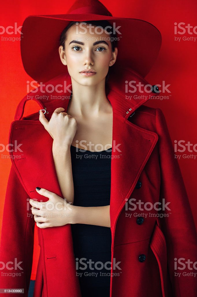 Beautiful girl with make-up wearing red coat and hat stock photo