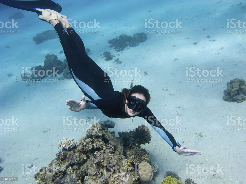 Beautiful girl with monofin looks toward underwater camera stock photo