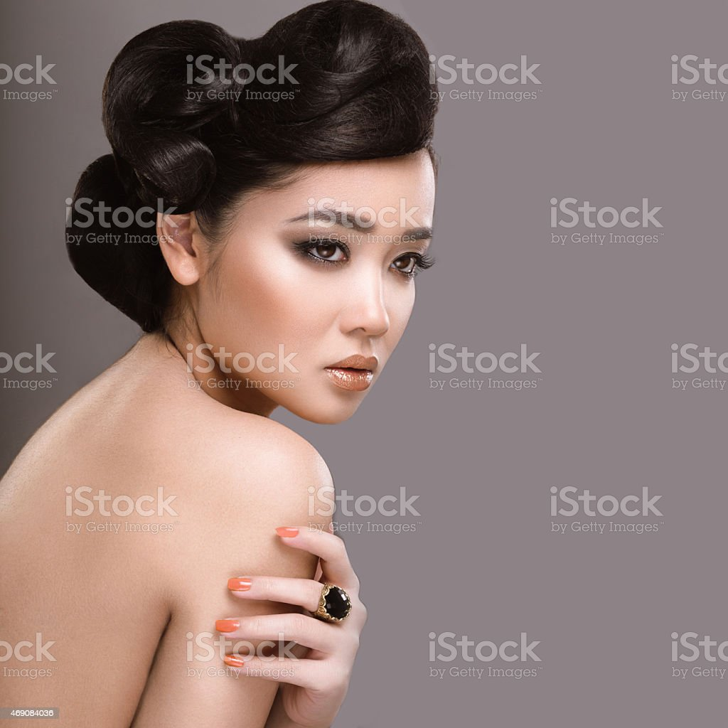 Beautiful girl with oriental type evening hair and makeup. stock photo