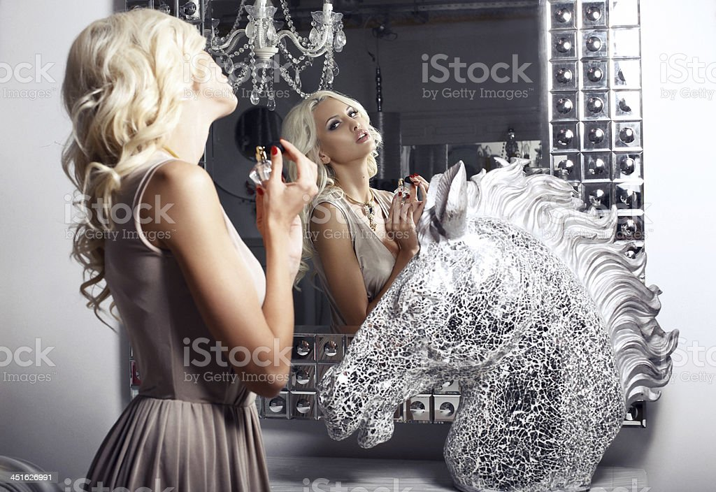 beautiful girl with perfume looking at the mirror stock photo