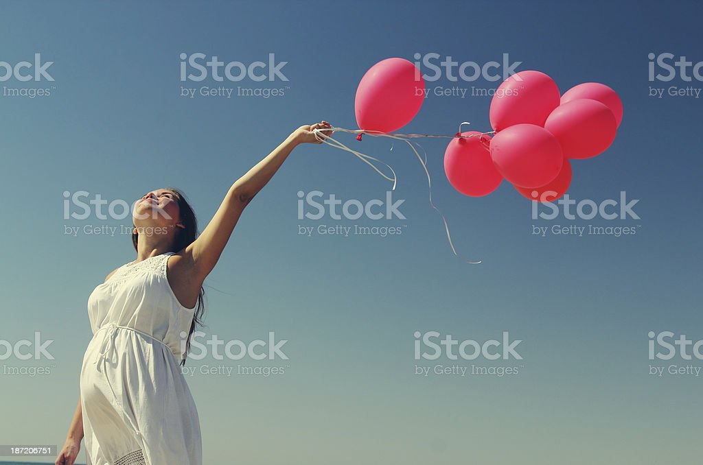 Beautiful girl with red balloon at blue sky background stock photo