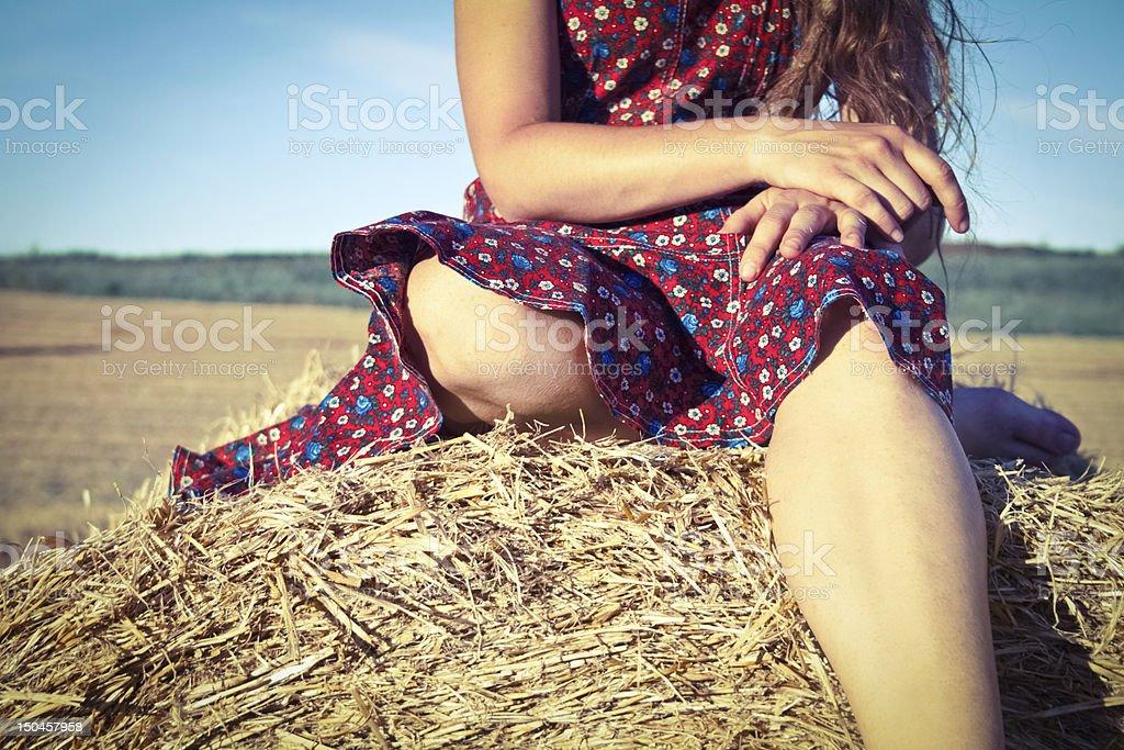 아름다운 소녀 적색 정장용 앉아 hay 베일 royalty-free 스톡 사진