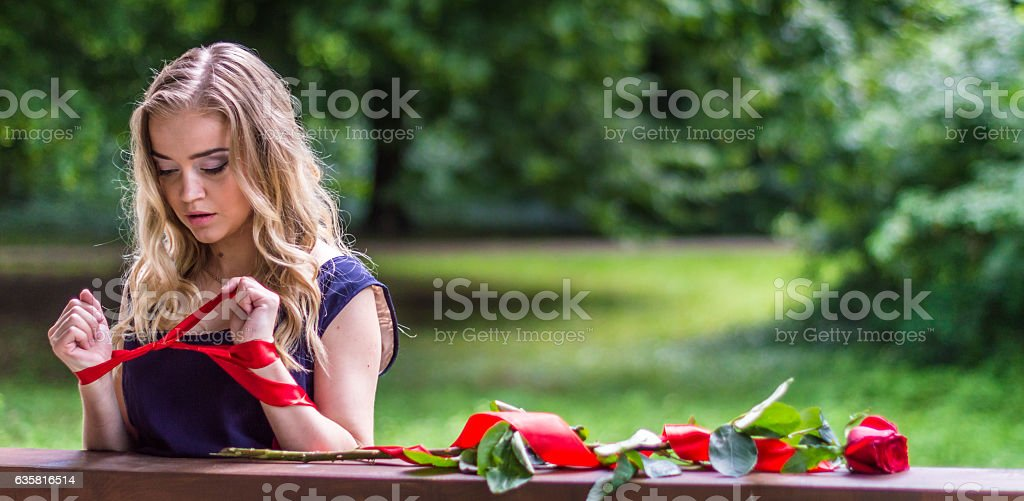beautiful girl with rose and red tape stock photo