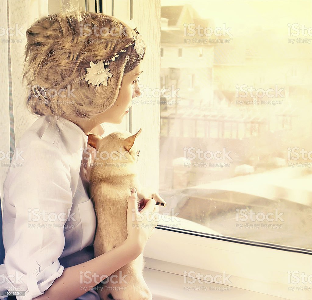 beautiful girl with small dog looking through window stock photo