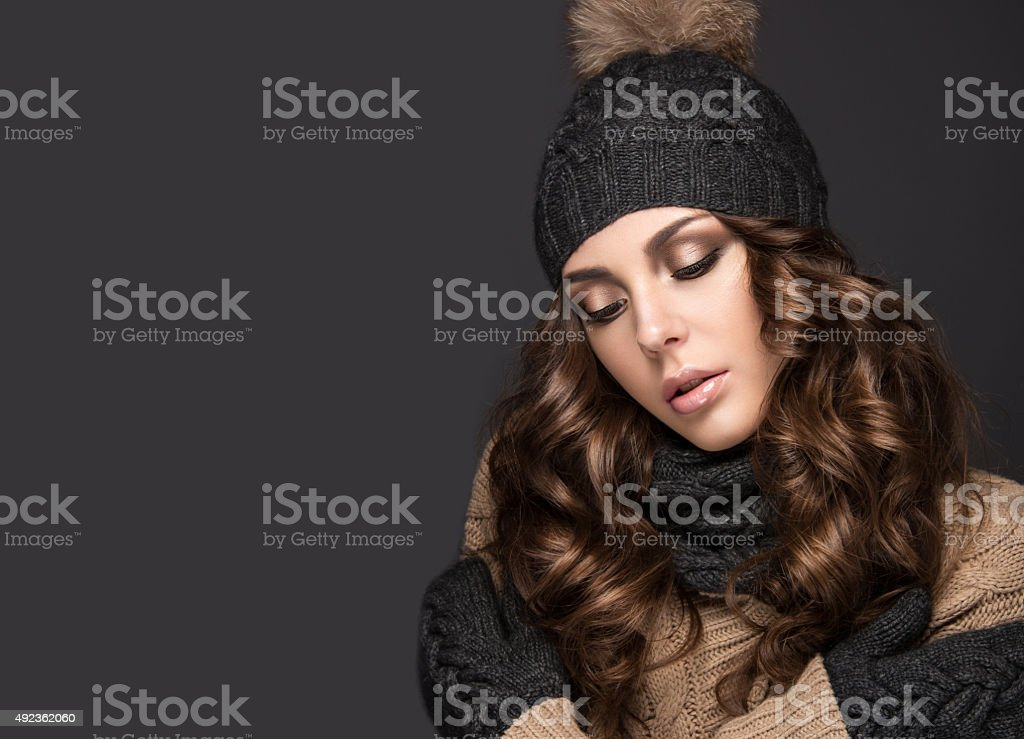 Beautiful girl with Smokeymakeup, curls in black knit hat. Warm stock photo