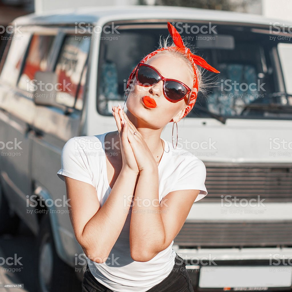 Beautiful girl with sunglasses and a red armband. Pin-Up Style. stock photo