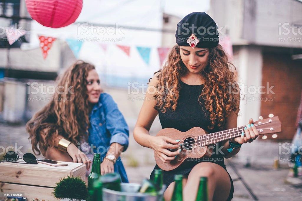 Beautiful girl with turban playing ukulele stock photo
