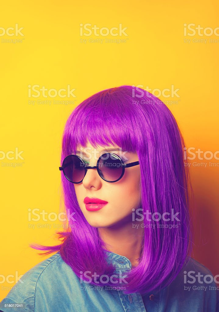 Beautiful girl with violet hair in sunglasses on yellow backgrou stock photo