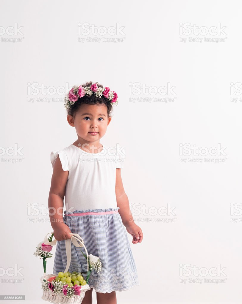 Beautiful girl with wreath in hair holding flower basket with fruits. stock photo