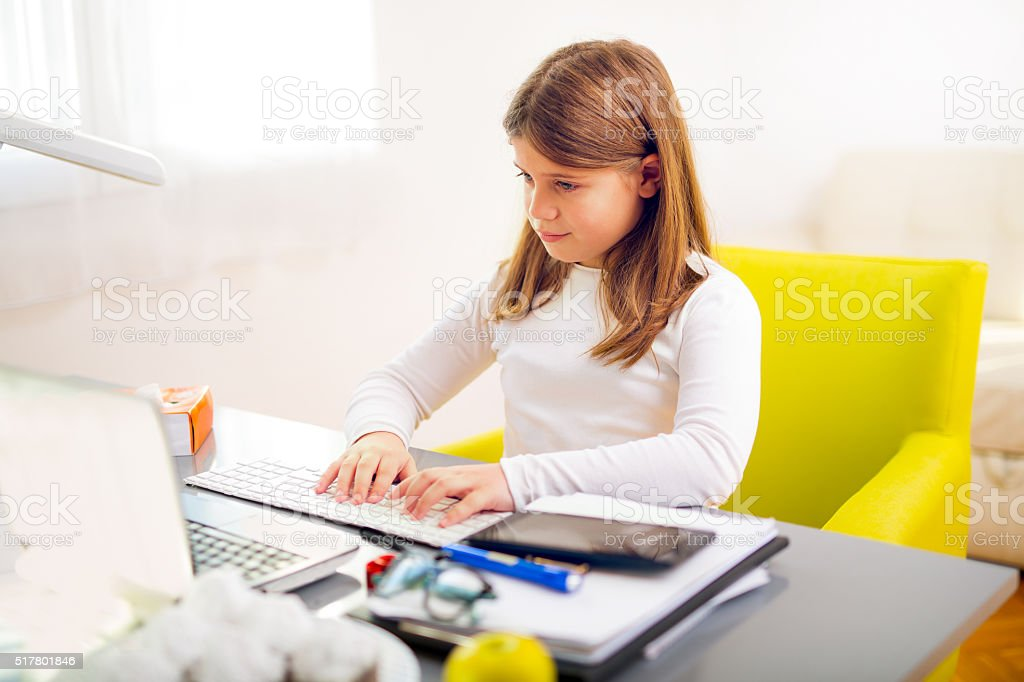 Beautiful girl working on her school project at home stock photo