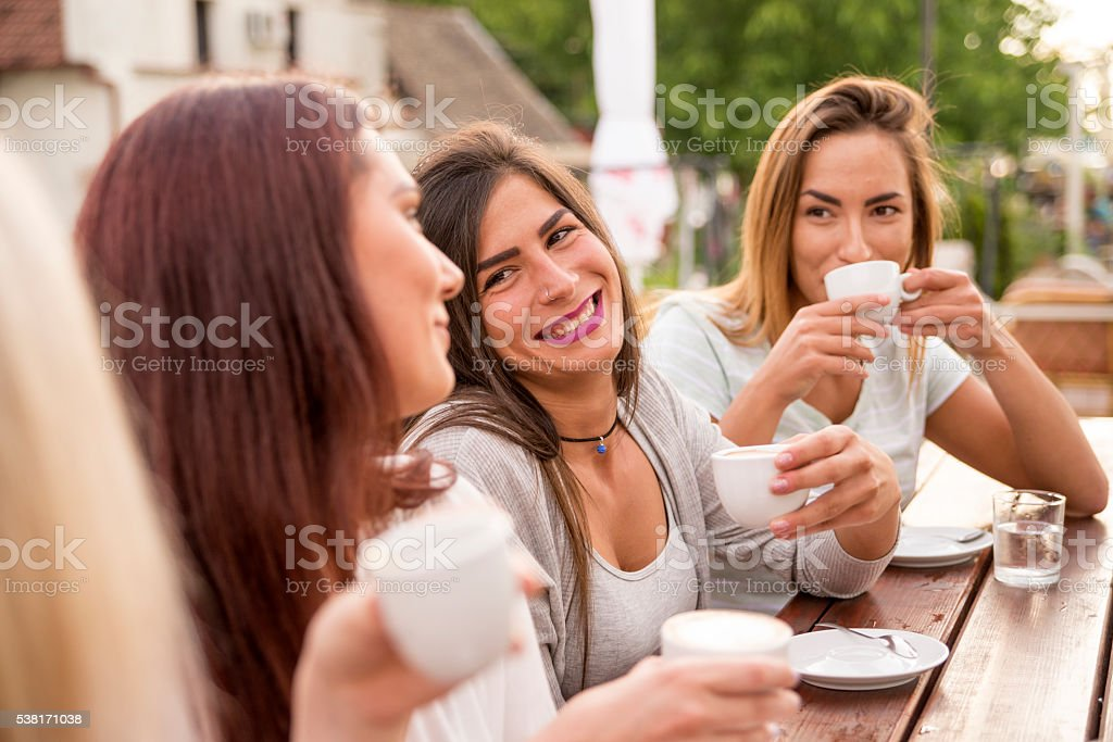 beautiful girls drinking coffee in cafe stock photo