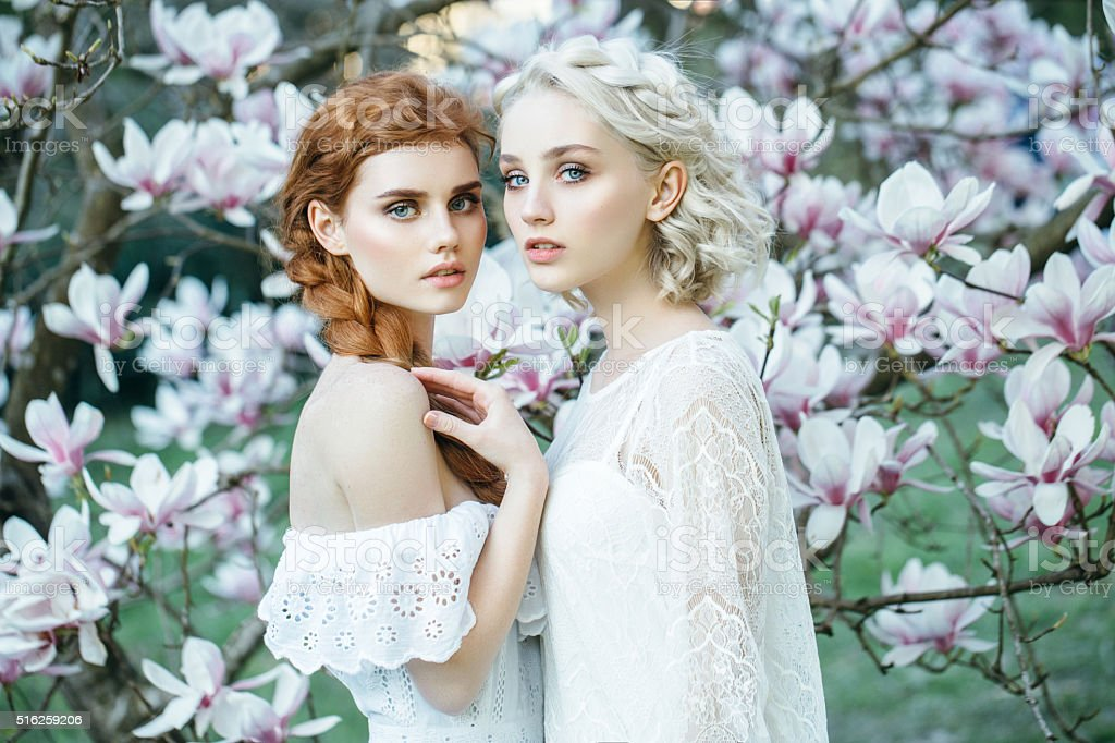 Beautiful girls on the background of spring bush stock photo