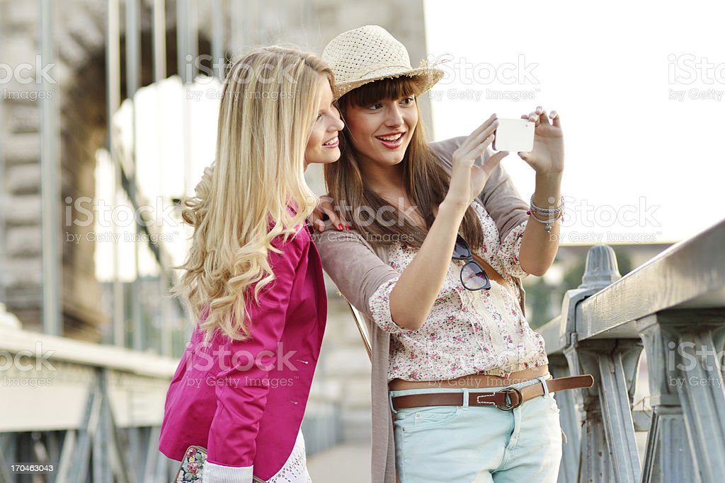 Beautiful girls photographing with mobile phone in the city royalty-free stock photo