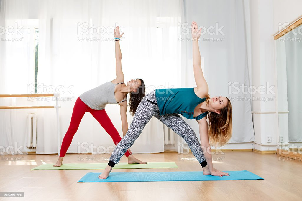 Beautiful girls showing triangle yoga pose in studio stock photo