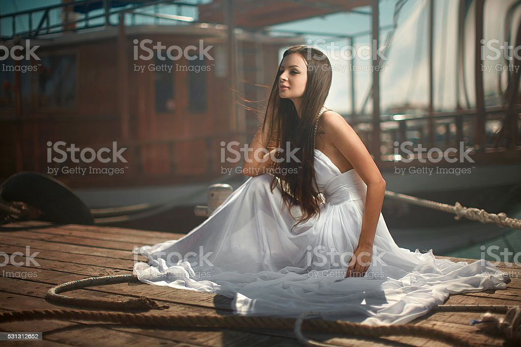 Beautiful, glamorous woman, girl sitting at pier in yacht club. stock photo