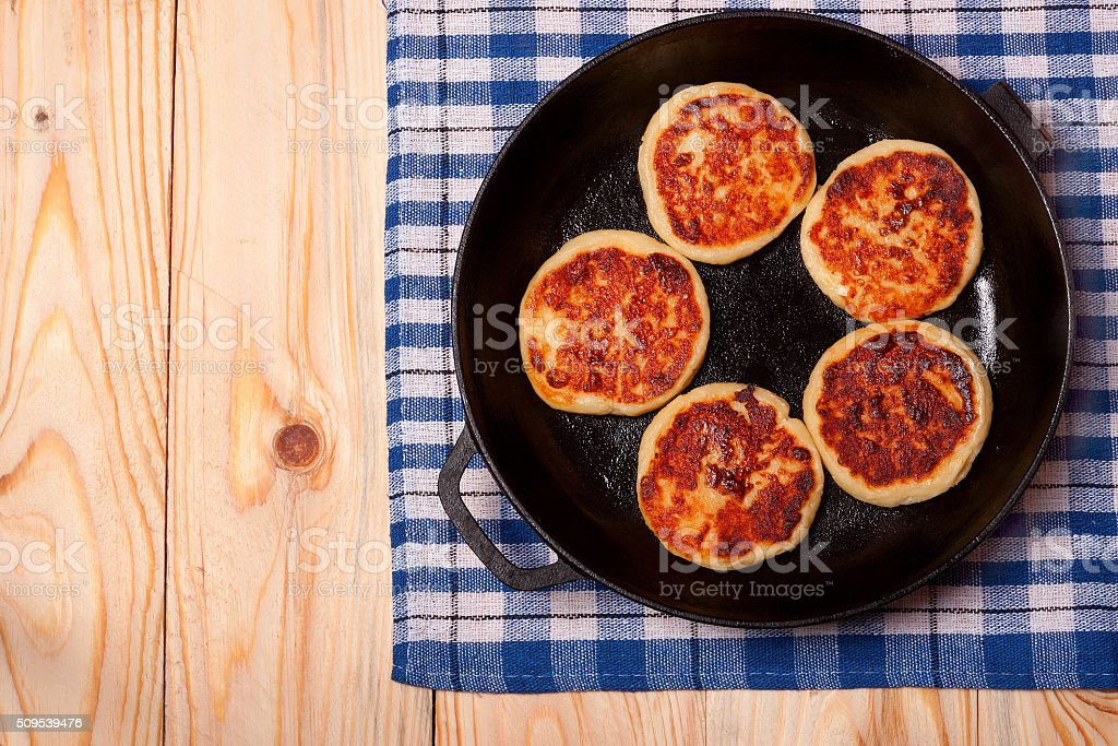 Beautiful golden cheese pancakes fried in a pan. Syrniki. stock photo