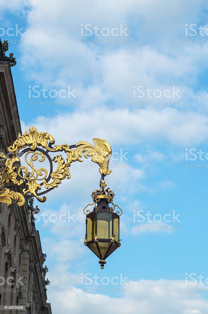 Beautiful golden decorative wrought lantern hanging on the wall stock photo