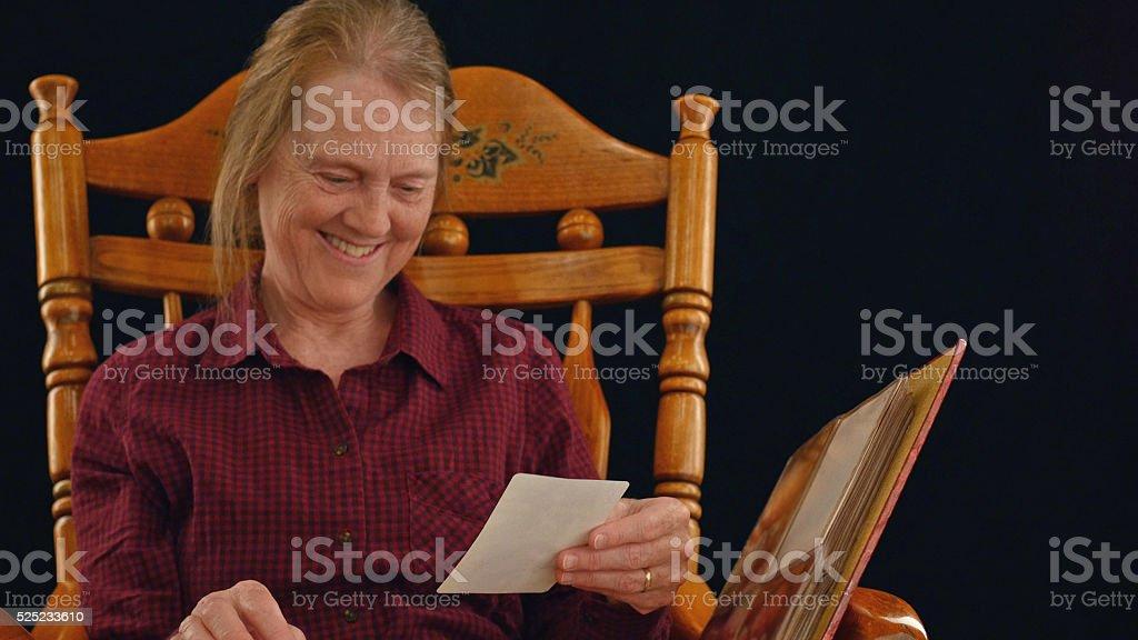 Beautiful grandmother looks through photo album stock photo