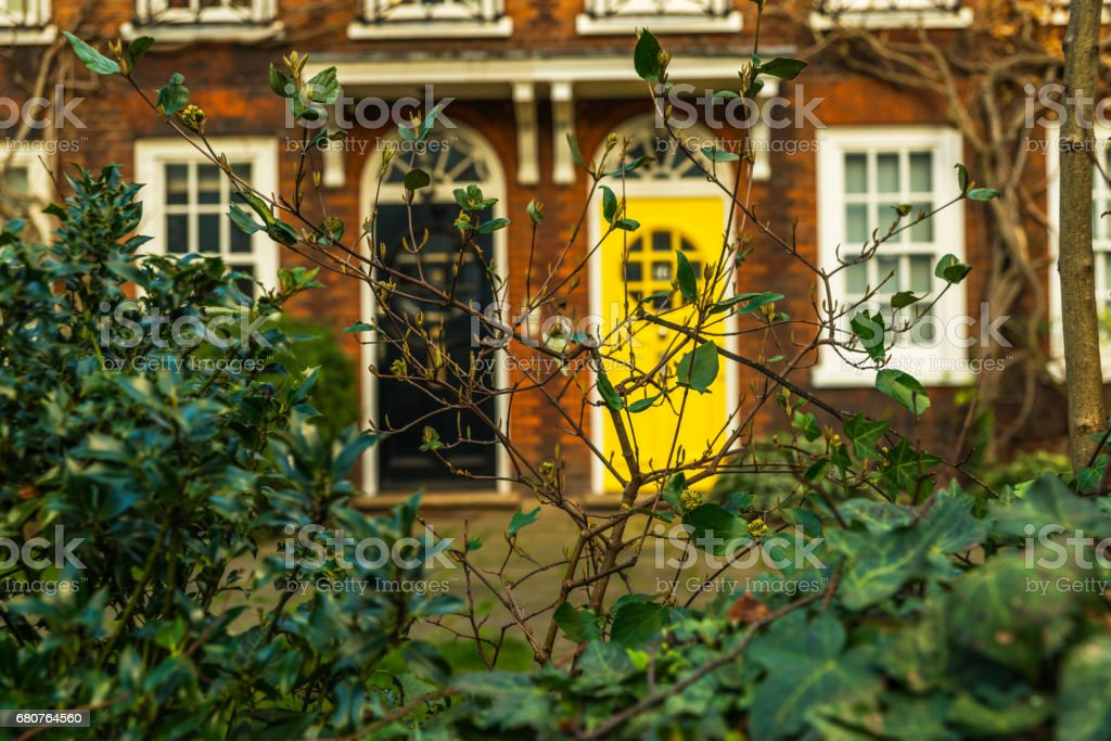 Beautiful green vegetation in the background brick facade of a typical English building, interesting black and yellow entrance doors stock photo