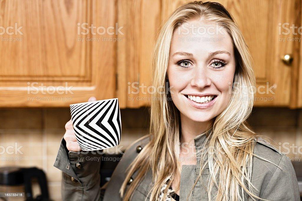 Beautiful green-eyed blonde smiles, holding coffee mug royalty-free stock photo