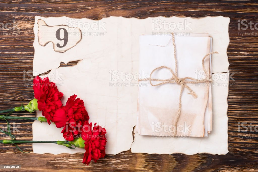 beautiful greeting card on may 9, the red flowers on the table on old paper stock photo