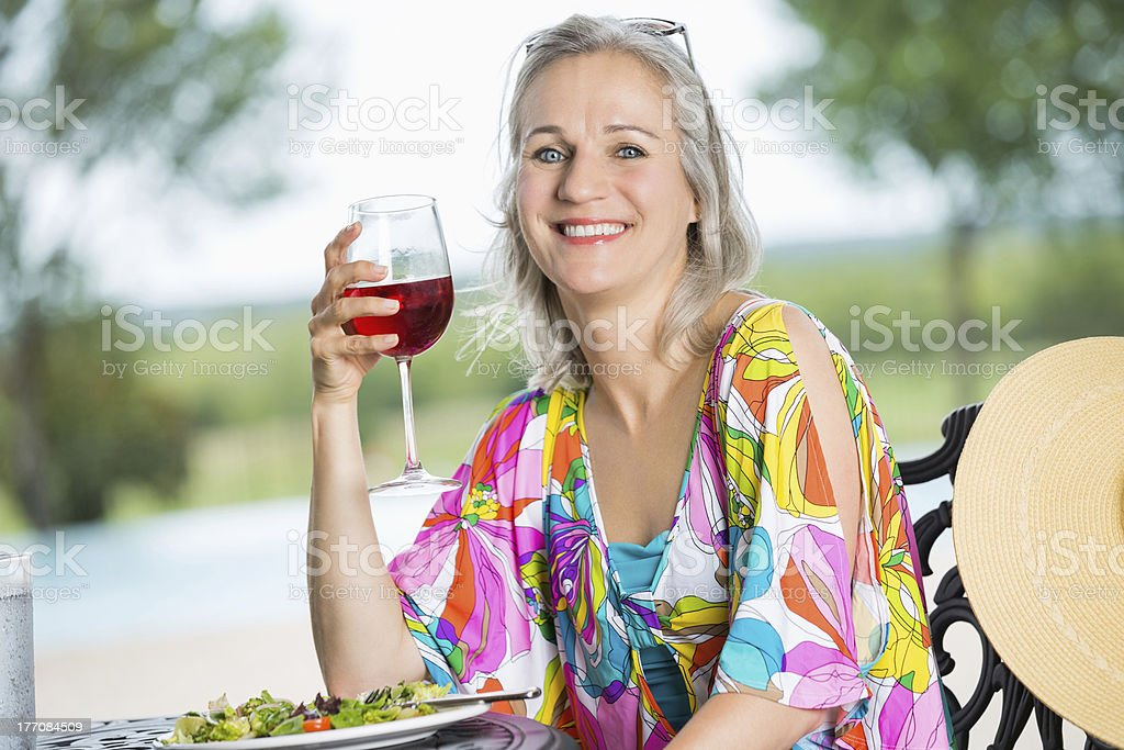 Beautiful grey haired woman having lunch by swimming pool royalty-free stock photo
