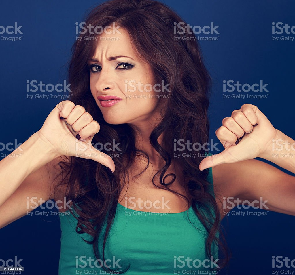 Beautiful grimacing woman with long hair showing refuse sign stock photo
