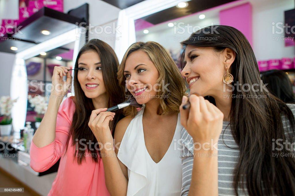 Beautiful group of women applying makeup stock photo