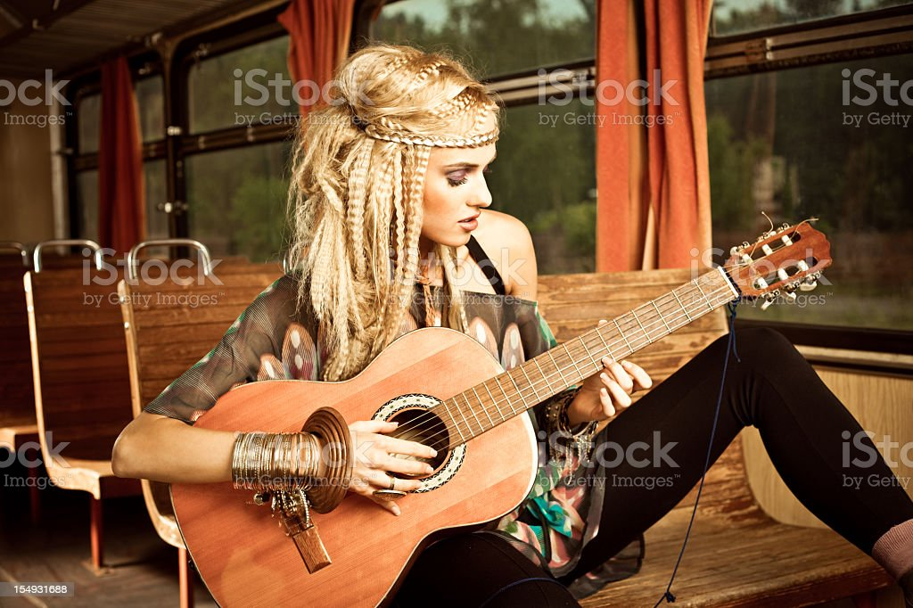 Beautiful guitarist in the vintage train royalty-free stock photo