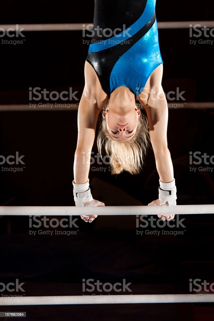 Beautiful gymnast pauses in a handstand atop uneven bars stock photo