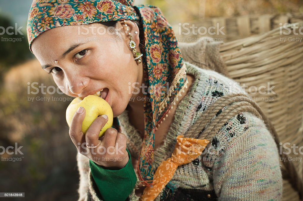 Beautiful, happy, Asian young woman carrying basket and eating apple. stock photo