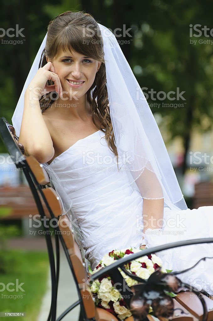beautiful happy bride in a white dress sitting on bench royalty-free stock photo