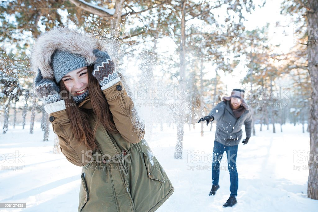 Beautiful happy couple throwing snowballs and having fun stock photo