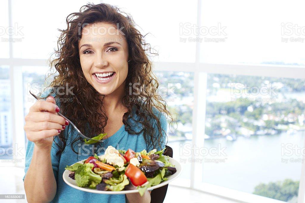 Beautiful happy female eating a salad stock photo