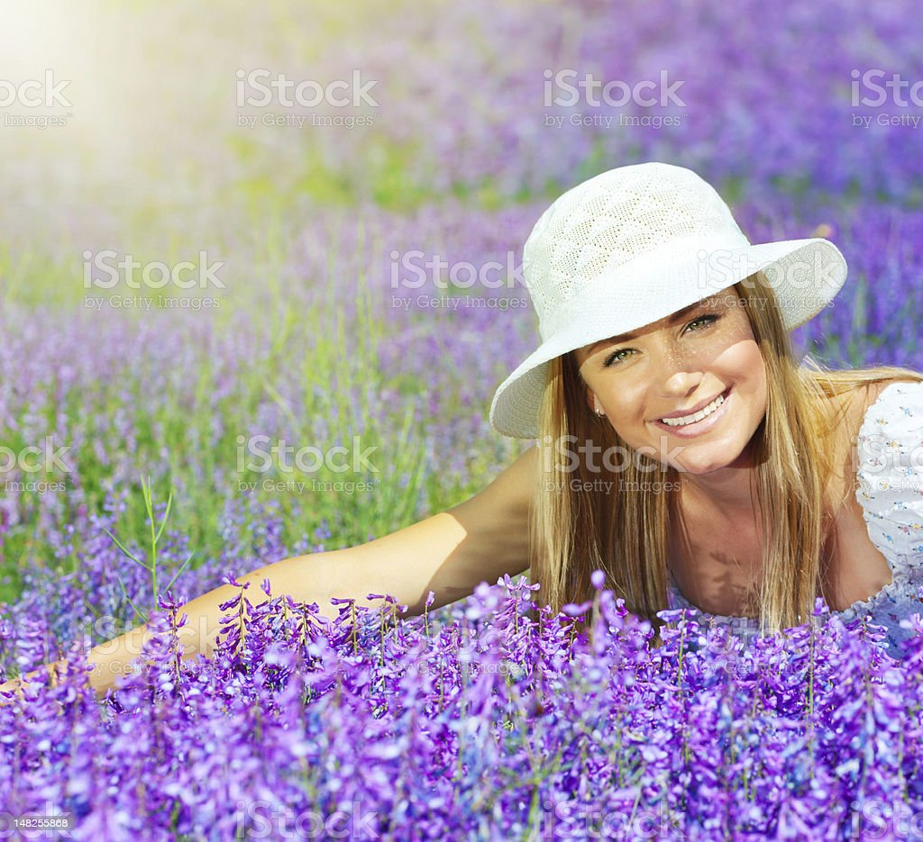 Beautiful happy female lying down on lavender field royalty-free stock photo
