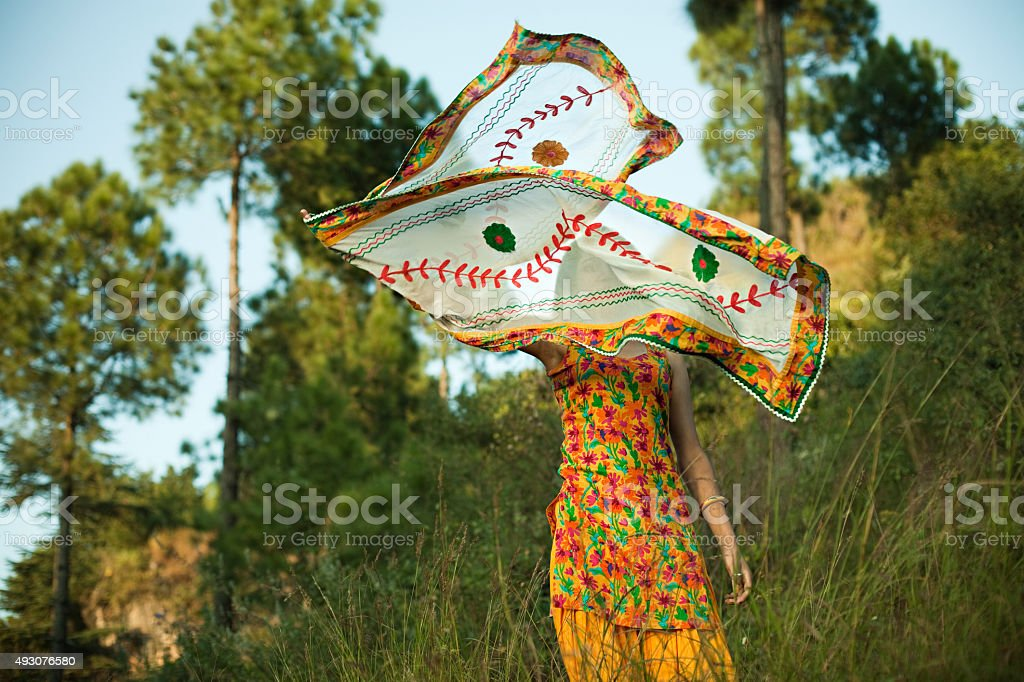 Beautiful happy Indian girl flying her dupatta in nature. stock photo