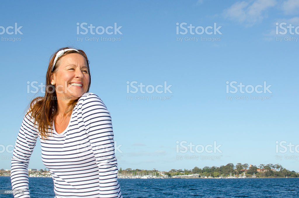 Beautiful happy mature woman coast background stock photo