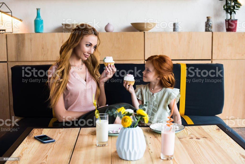 beautiful happy mother and daughter eating delicious cupcakes in cafe stock photo