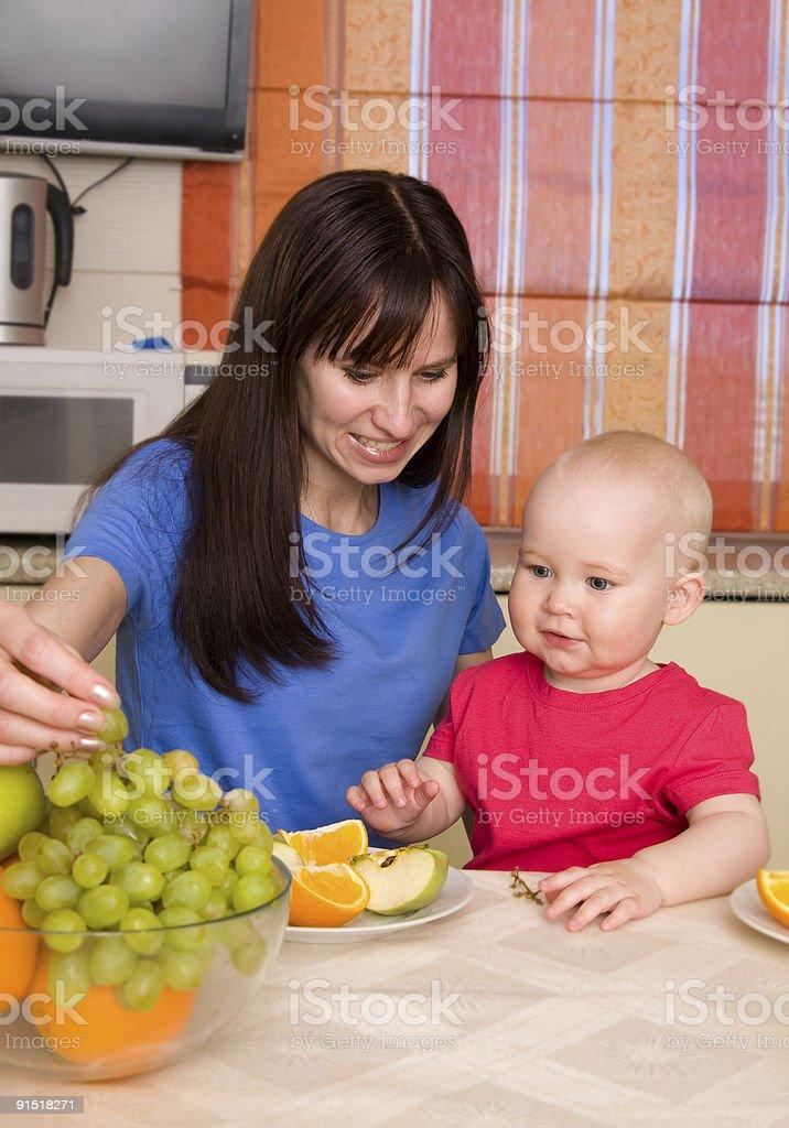 Beautiful happy mum with son eat fruit royalty-free stock photo