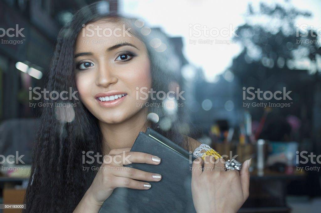 Beautiful, Happy teenage girl with book behind glass window. stock photo