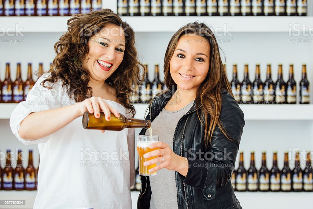Beautiful happy woman pouring beer stock photo