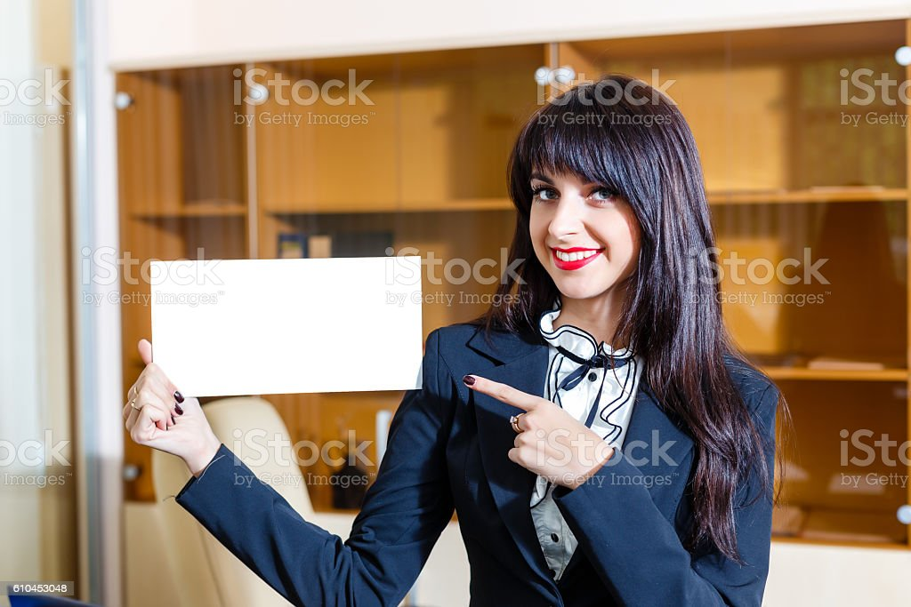 Beautiful happy woman showing empty card in office stock photo