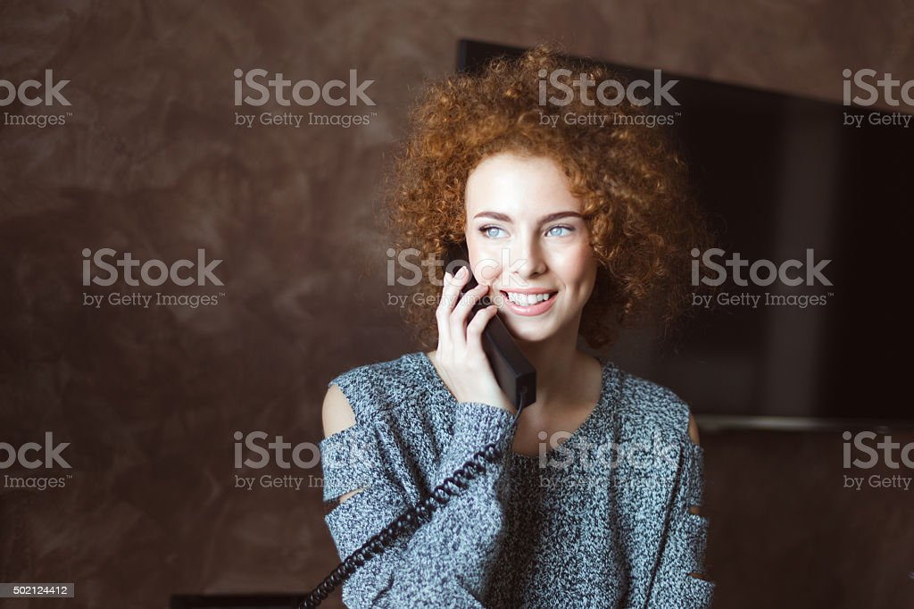 Beautiful happy woman talking on landline telephone in the room stock photo