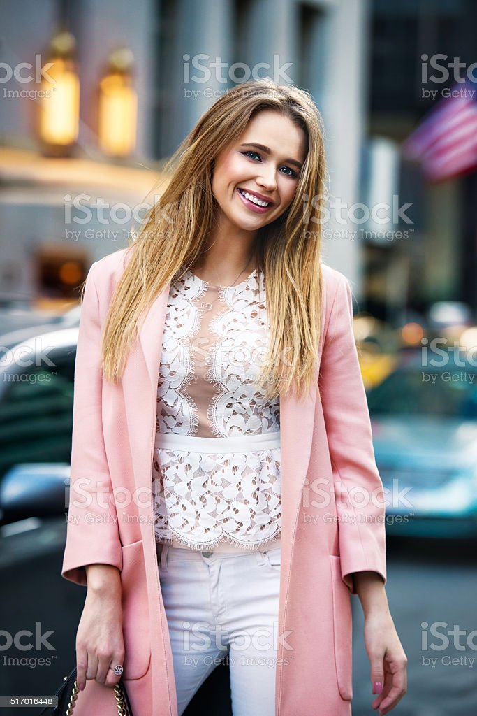 Beautiful happy woman with perfect smile standing in city street stock photo