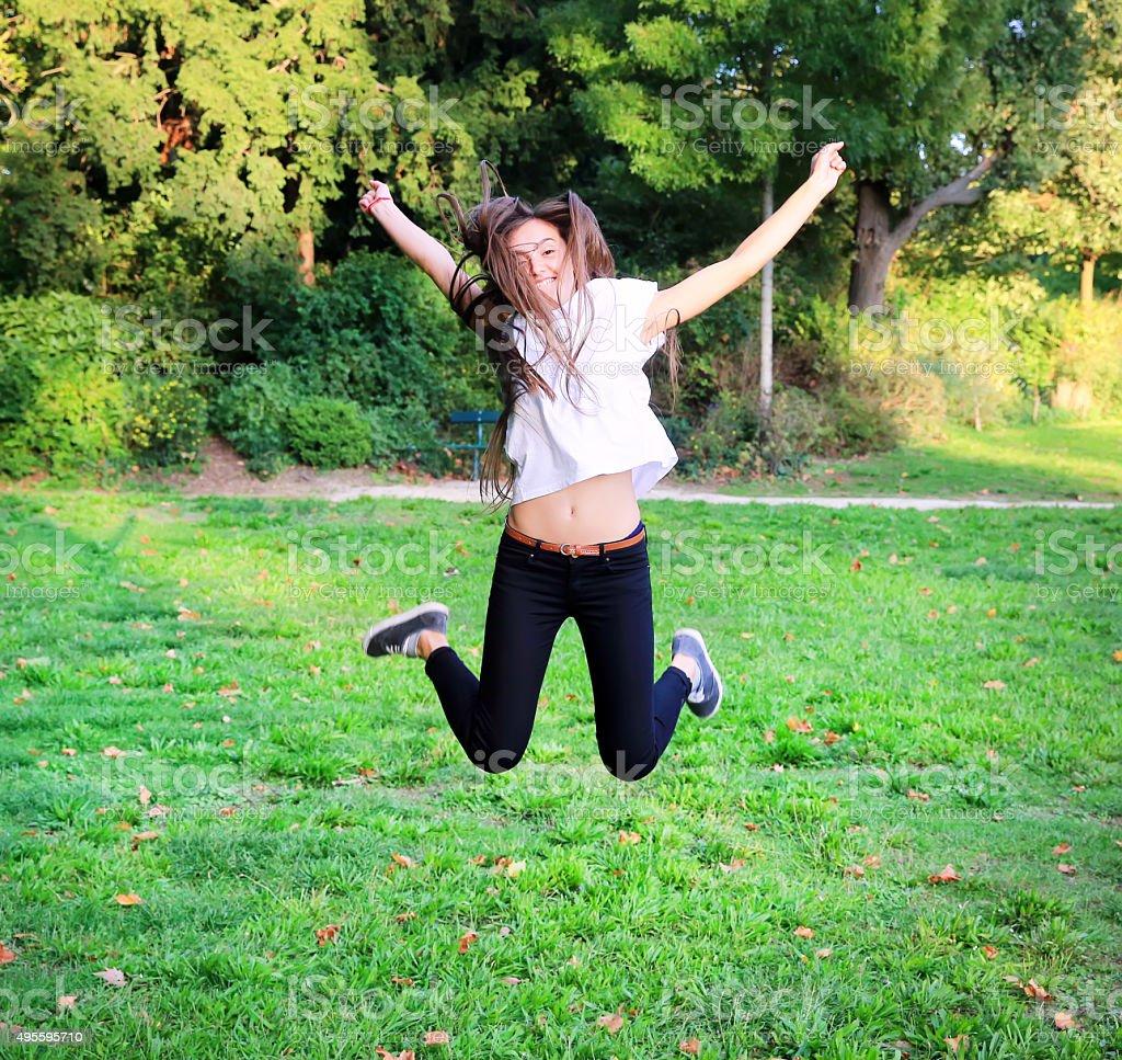 Beautiful happy young teen girl jumping stock photo