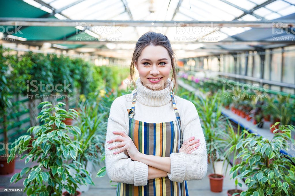 Beautiful happy young woman gardener in colorful striped apron stock photo