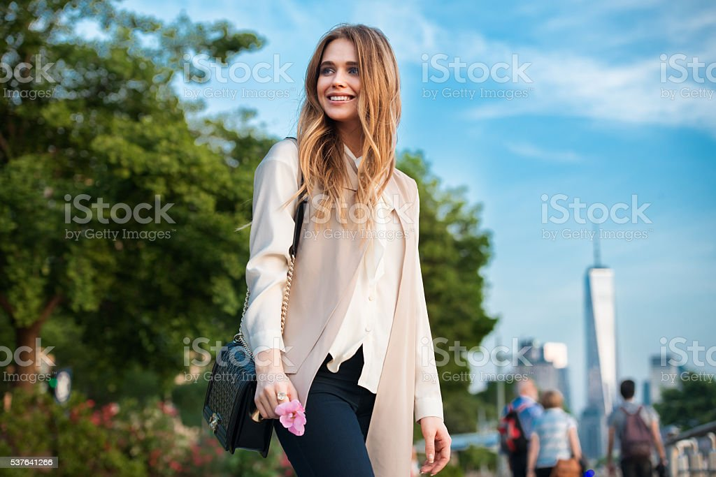 Beautiful happy young woman walking in the city park stock photo