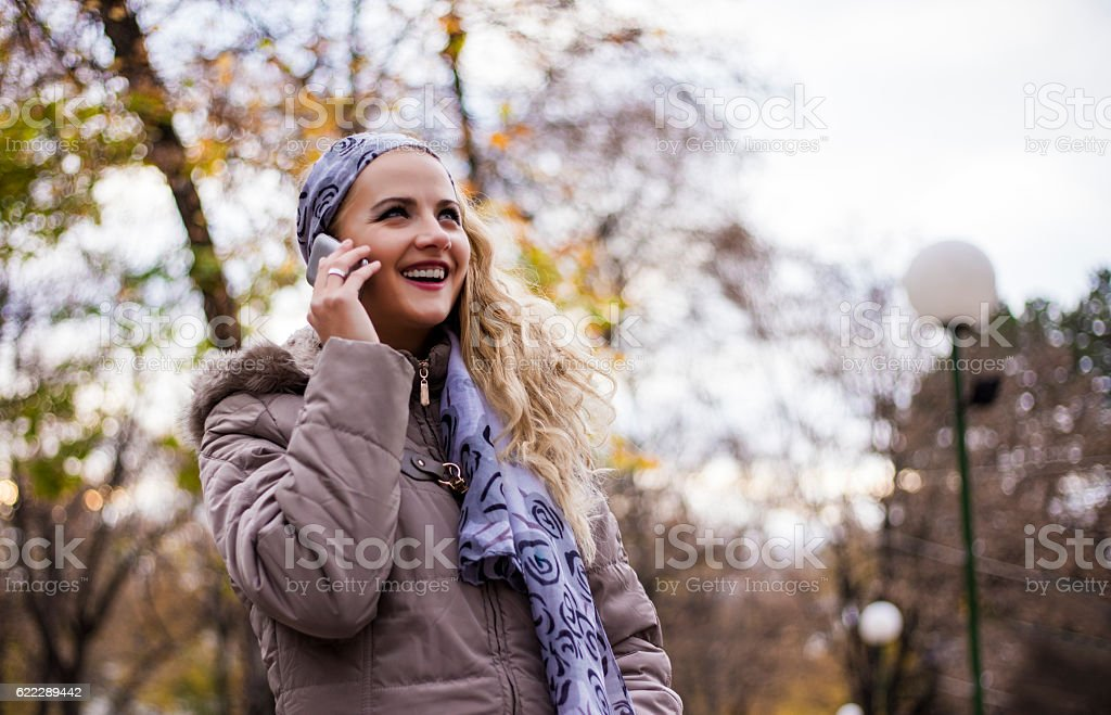 Beautiful happy young woman with smartphone. stock photo